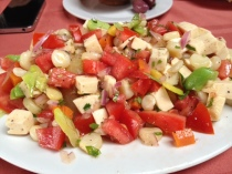 A salad of salty cheese, fava beans, tomatoes, and peppers